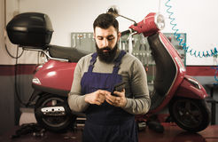 Worker counting sum for his repairing motorcycle. Smiling man worker counting sum for his repairing motorcycle in workshop Stock Photography