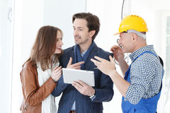 Worker and couple at construction site. Worker and couple using tablet pc at construction site Royalty Free Stock Photography