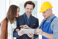 Worker and couple at construction site. Worker and couple using tablet pc at construction site Royalty Free Stock Image