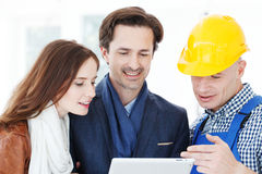 Worker and couple at construction site. Worker and couple using tablet pc at construction site Stock Images