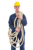 Worker in coverall and yellow helmet with large thick rope Stock Photos