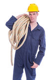 Worker in coverall and yellow helmet with large thick rope Stock Photography