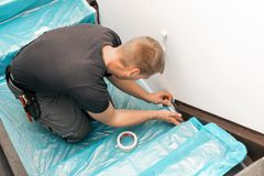Worker covering stairs carpet with masking film. Before home improvement works Royalty Free Stock Image