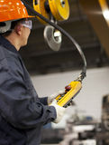 Worker and crane hook. Worker holding crane hook button working in factory with safety workwear Stock Images