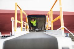 Worker Crouching In Airplane With Luggage Conveyor In Foreground Royalty Free Stock Photos