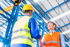 Worker and customer having agreement in factory Stock Photography