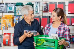 Worker With Customer Holding Tools In Hardware. Happy senior worker with female customer holding tools in hardware shop Stock Photography