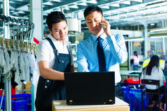 Worker and customer service of a factory. Worker or production manager and customer service, look on a laptop in a textile factory and help on the phone stock photography