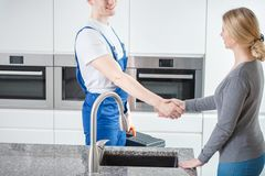 Worker and customer shaking hands. Young worker shaking hands with his female customer Stock Photos