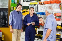 Worker With Customers In Hardware Shop Royalty Free Stock Photography