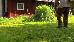 Worker cut lush grass in village with petrol trimmer, tripod pan stock footage