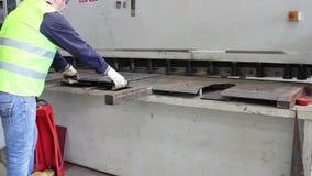 Worker cut metal plate on big machine stock video footage