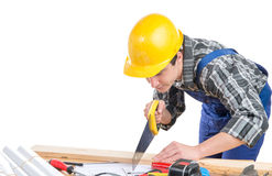 A worker cut a plank  with a hand saw Royalty Free Stock Photo