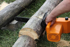 Worker cuts a beam by electric chain saw Stock Photography