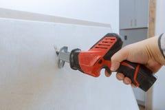 Worker cuts with a dirty saw drywall cutting gypsum board