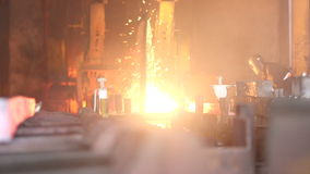 Worker cuts fiery steel blocks. Steel making - male worker cuts fiery steel blocks at the factory stock footage