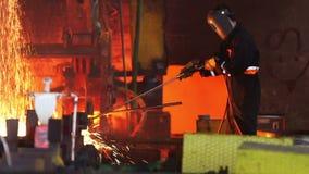 Worker cuts fiery steel blocks. Steel making - male worker cuts fiery steel blocks at the factory stock video footage