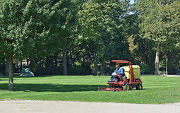 Worker cuts grass in Cinquantenaire Parc in Brussels stock image