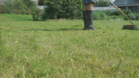 Worker cuts the grass with a lawnmower outdoors. The worker cuts the grass with a lawnmower outdoors stock footage
