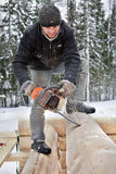 Worker cuts log home lateral grooves using chainsaw Royalty Free Stock Image