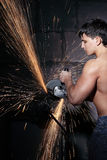 Worker cuts metal. Muscular worker cuts metal with sparks. Circular metal cutter Stock Photography