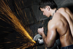Worker cuts metal. Muscular worker cuts metal with sparks. Circular metal cutter Stock Photo