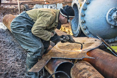 Worker cuts metal cutting torch. Worker welder makes billets of metal for the production of repair and rehabilitation works on the water supply pipe. Cutting Royalty Free Stock Photography