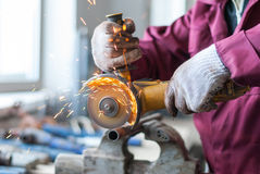 The worker cuts a metal pipe. Royalty Free Stock Photography