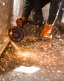 Worker cuts a metal pipe with sparks Royalty Free Stock Image