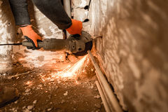 Worker cuts a metal pipe with sparks Royalty Free Stock Photos