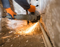 Worker cuts a metal pipe with sparks Stock Images