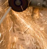 Worker cuts a metal pipe with sparks Royalty Free Stock Images