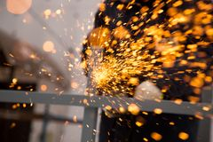 The worker cuts the metal with sparks Stock Images