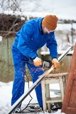 Worker cuts panel frame for installation of solar panels. Winter Royalty Free Stock Image