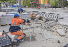 Worker cuts paving tiles on the machine tool Royalty Free Stock Photography