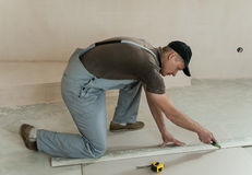 Worker cuts a piece of drywall. With a knife and a ruler Stock Image
