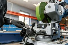 Worker cuts a piece of material with a circular saw machine. Industrial engineer working on cutting a metal and steel. With compound mitre saw with sharp royalty free stock photography