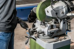 Worker cuts a piece of material with a circular saw machine. Industrial engineer working on cutting a metal and steel. With compound mitre saw with sharp royalty free stock photos