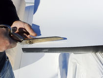 Worker cuts PVC sheet with a scissors Stock Photography