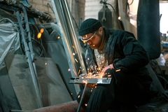 The worker cuts the steel with an electric grinding wheel stock photography
