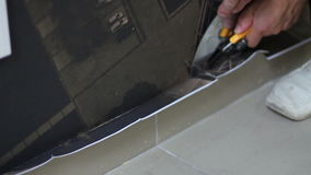 Worker cuts wallpaper near the floor after wallpapering stock video footage