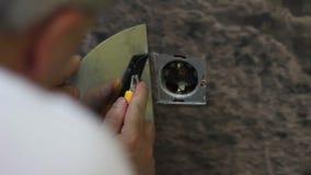 Worker cuts wallpaper near the power socket after wallpapering stock video footage