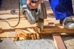 Worker cuts wood bars. Carpenter using an electric saw cutting small wooden figures Stock Images