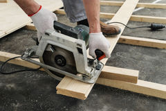 Worker cuts wooden floorboards. Royalty Free Stock Photo