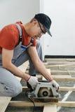 Worker cuts wooden floorboards. Stock Photo