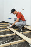Worker cuts wooden floorboards. Royalty Free Stock Images