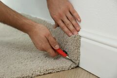 Worker with cutter knife installing new carpet indoors, closeup