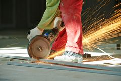 Worker cutting bar by grinding machine Stock Images