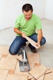 Worker cutting ceramic floor tiles Stock Image