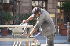 Worker cutting granite tiles with an diamond electric saw blade royalty free stock image